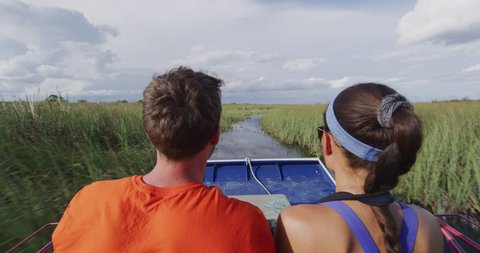 Everglades Airboat tour in Everglades in Florida - tourists couple on private air boat tour. Airboat tours are a famous tourist attraction in the Everglades. RED cinema camera in SLOW MOTION.