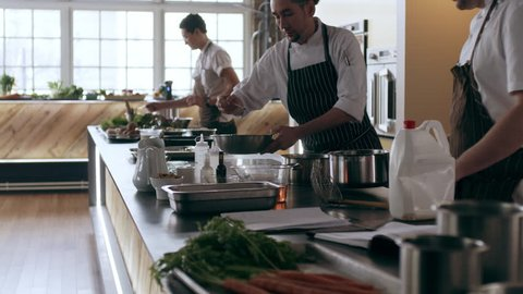 Three professional chefs cooking and preparing food in pots and pans in interior kitchen with soft day lighting. Medium shot on 4k RED camera on a gimbal in slow motion.
