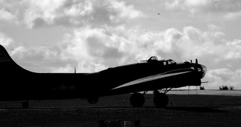 WWII B17 airplane turning on runway - silhouetted in black and white