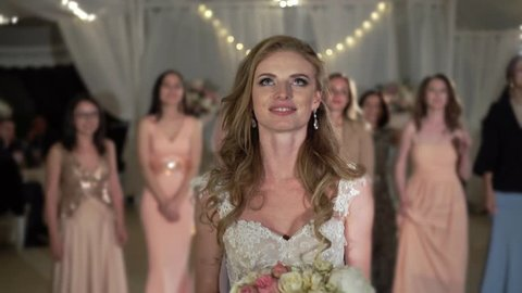 Bride throws traditional bouquet for girls at wedding celebration party at the evening
