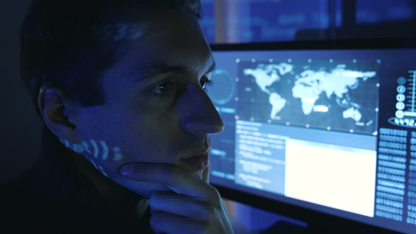 Close-up portrait of a Man Professional Developer Programmer in a data center filled with monitor screens. Hacker works at a computer at night in a dark office. | Shutterstock HD Video #1022084983