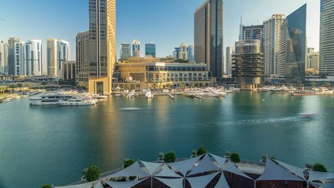 Aerial vew of Dubai Marina with shoping mall, restaurants, towers and yachts timelapse, United Arab Emirates. Top view of canal at evening before sunset