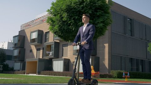 Full shot - Adult male in business attire riding with electric scooter to work