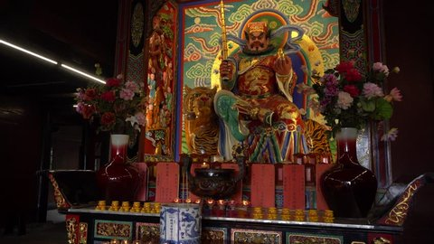 Statue of Buddha in temple with candles
