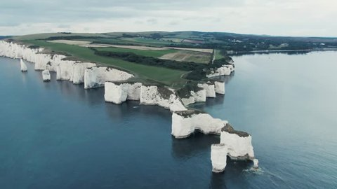 4K - Aerial Footage of Old Harry Rocks - England - Sunrise - Drone Revealing the land.