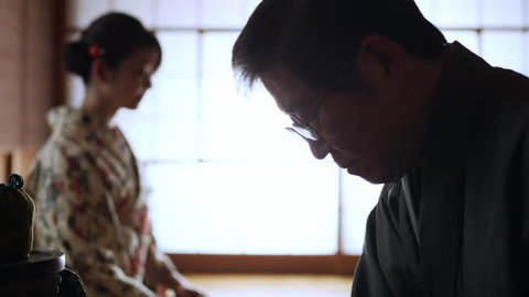 Lady waits while tea master prepares a bowl of tea during ceremony in a traditional Japanese home with soft day lighting. Close up shot on 4k RED camera.