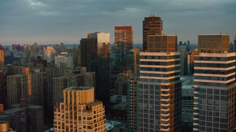 Aerial view of tall buildings and skyscrapers of downtown Manhattan, New York, during sunset in winter. Shot on 4k RED camera on helicopter