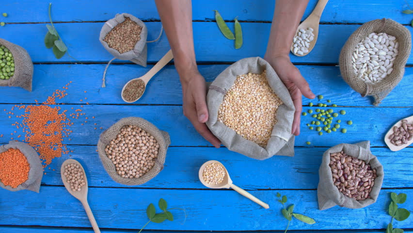 Legumes on wooden ecological background. Beans are on a blue wooden table. Hands take woven bag with peas from table.  | Shutterstock HD Video #1022202523
