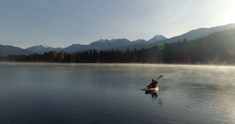 Cinematic Aerial View Of Man Paddling On A Misty Lake In The Mountains At Sunrise | Shutterstock HD Video #1022272213