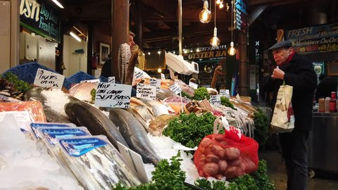 BOROUGH MARKET, LONDON - JANUARY 10, 2019: A customer purchases seafood from a fishmonger at Borough Market in Southwark, London, UK.