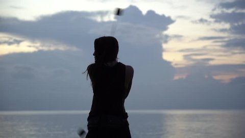 KOH PHANGAN, THAILAND - DECEMBER 19, 2018: An unidentified girl skillfully juggling poi on beach near sea water at sunset on Koh Phangan island, Thailand , slow motion