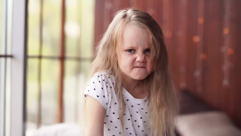 Naughty bad mannered little girl with blond hair and freckles makes a very angry grumpy face at the camera, , slow motion
