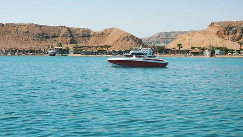 Sharm el Sheikh, Egypt - October24, 2018: Splendid view of a modern motorboat anchored near the Red Sea coastine with small hotels, hills, and palms on a sunny day in slow motion