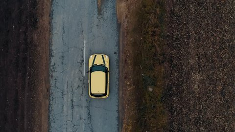 Yellow car on the road. Sky view of autumn road with cars. Aerial view country road in autumn forest. Autumn car road in forest top view. Aerial landscape.