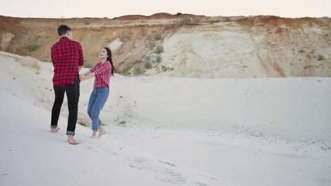 Young couple run up to the top of a sand dune embracing each other in love, sand dunes. Couple of lovers walking on the each at sunset.
