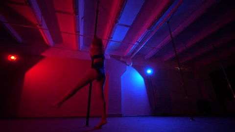Adult sexy woman dancing dance in an intimate setting. Silhouette of a sexy woman dancing on red background. Pole dance. Pole dance from an old woman