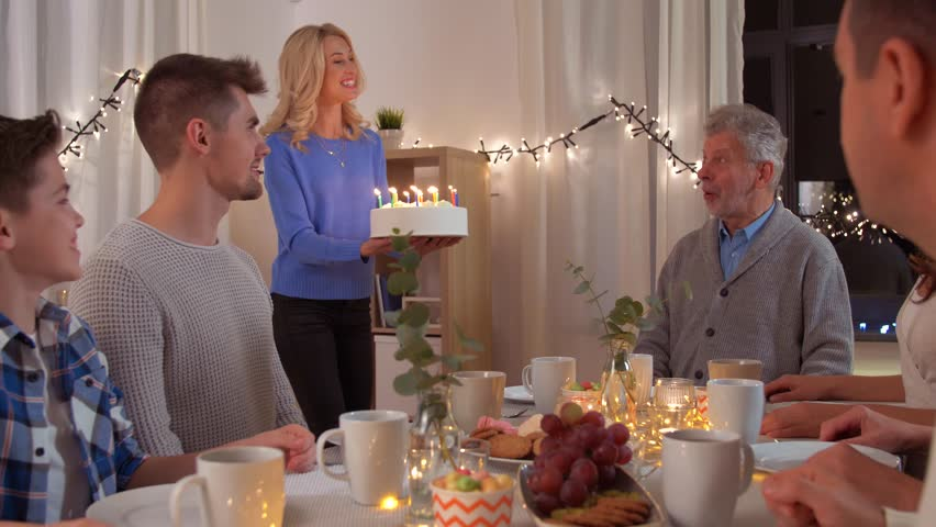 Celebration and family concept - happy grandfather blowing candles on birthday cake at dinner party at home | Shutterstock HD Video #1022556553