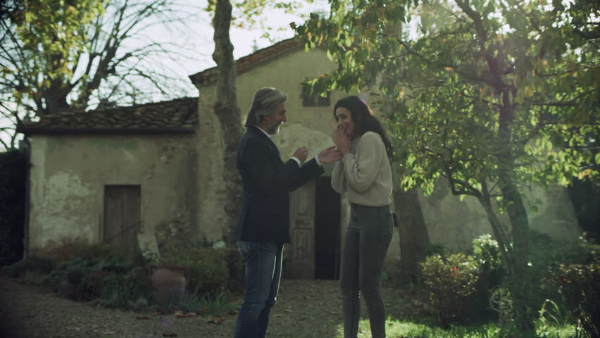 Loving Italian man proposes to his girlfriend and gives her a ring and they hug happily in a beautiful yard with a house in Tuscany with bright natural lighting. Wide shot on 4k RED camera.