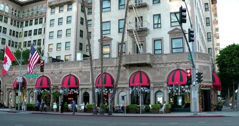 BEVERLY HILLS, LOS ANGELES, CALIFORNIA - SEPTEMBER 2, 2018: Luxury cars driving near Beverly Wilshire Hotel landmark and Rodeo Drive in Beverly Hills, Los Angeles, California, 4K