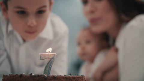 Boy blowing candle on birthday cake at family party in slow motion. Portrait of boy dream wish looking at birthday cake with number seven. Family happy birthday party concept
