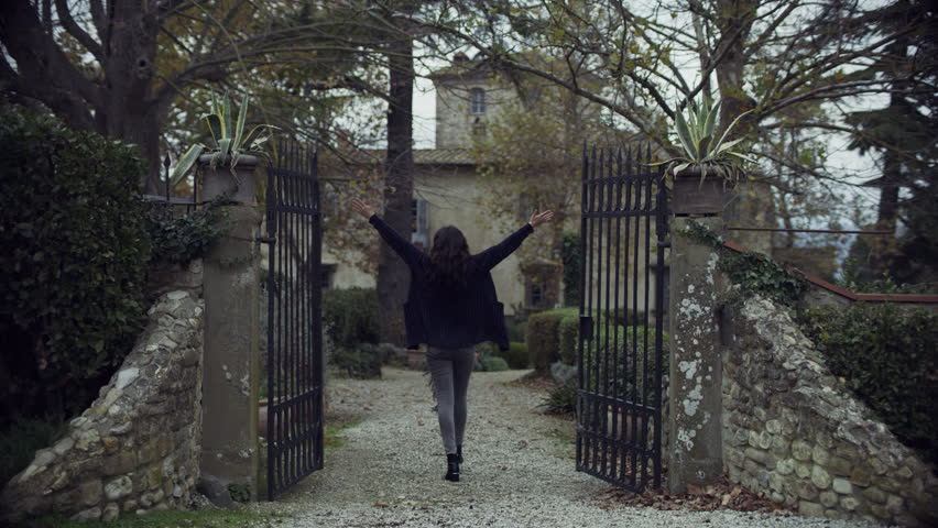 "Joyful Italian woman walking up to a gate with a ""Sold"" sign, throws it away and walks up to her new dream house in Tuscany with soft overcast light. Wide shot on 4k RED camera."