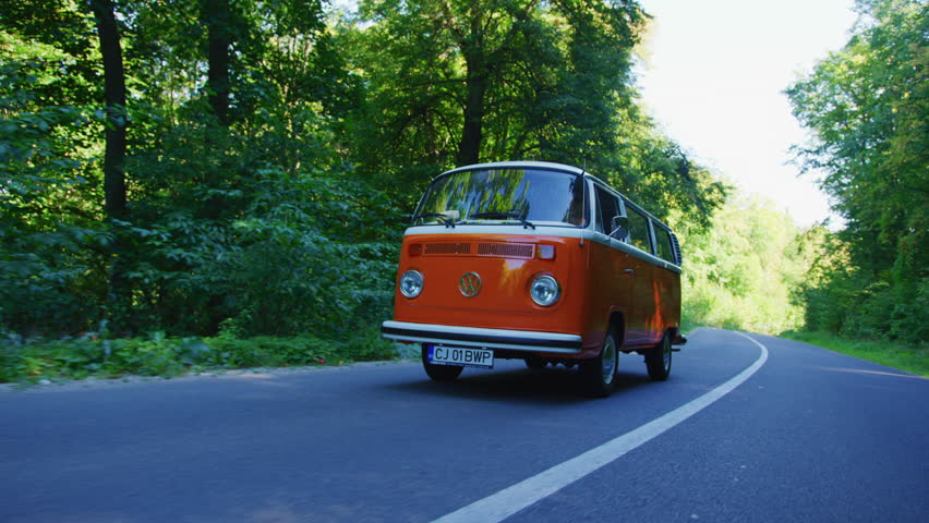 Driving a VW bus on a forest road.