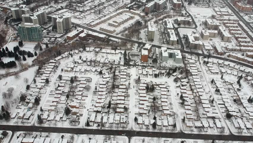 Aerial drone view of roads and houses winter landscape. Winter city streets from a bird eye view. Top perspective of  snow covered buildings. Roads, lawns, cars and trees covered with snow from above.