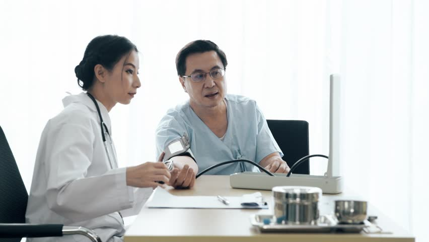 Doctor with patient. Young female medical doctor talking to a senior patient at hospital, measuring blood pressure. Senior care medical and insurance concept. | Shutterstock HD Video #1022583433