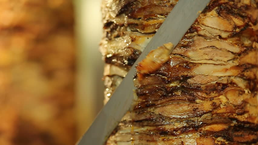 A cook cuts meat to make shawarma, gyros, doner kebab. Cooking meat on a skewer | Shutterstock HD Video #1022588293