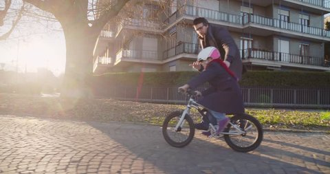 Daughter child girl learning riding bycicle with dad teaching in city.Growing,childhood,active safety family.Sidewalk urban outdoor.Warm sunset cold weather backlight.4k slow motion 60p side video