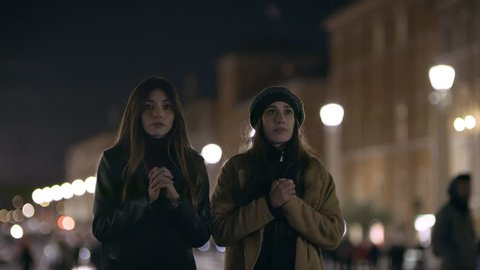 Religious Italian women walk up to a basilica and doing the sign of the cross, praying, and walking away together at the Vatican, with soft nighttime lighting. Wide shot on 4k camera