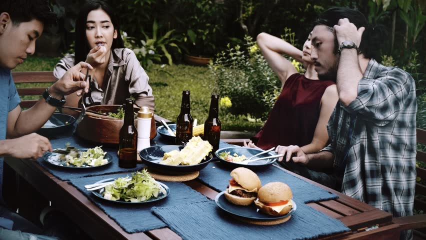 Friends enjoying outdoor food together. Group of Asian, chinese, thai friends having dinner together with beer, talking. House party concept. | Shutterstock HD Video #1022636773