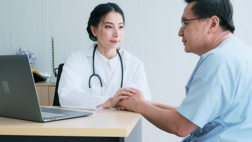 Doctor with patient. Young female medical doctor talking to a senior patient at hospital. Looking at her laptop to discuss medical examination result. Senior care medical and insurance concept. | Shutterstock HD Video #1022636863
