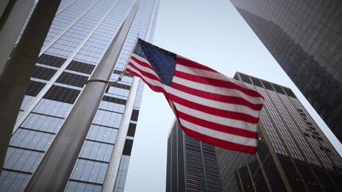 A United States American flag with skyscrapers in the background shot during the day from a low angle waving in the wind.