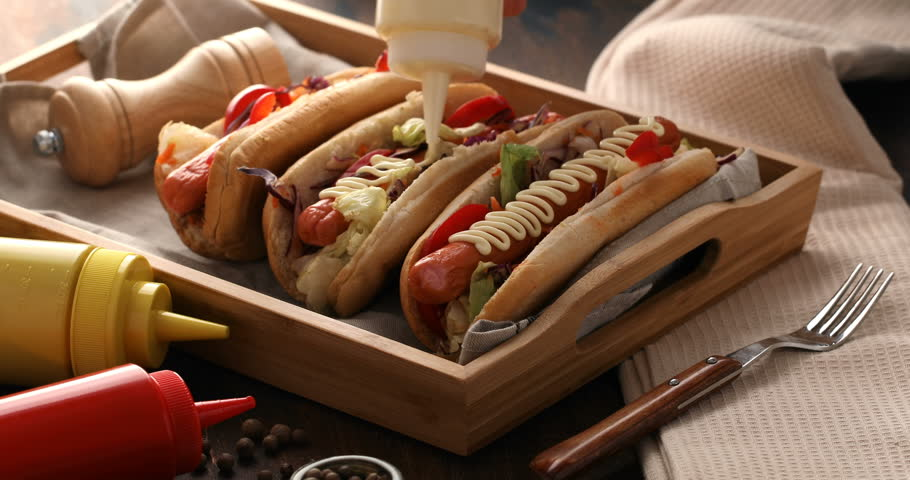 Hot dogs with a sausage on a fresh rolls garnished with mustard and ketchup. Men hand hand pouring hotdog with sauce