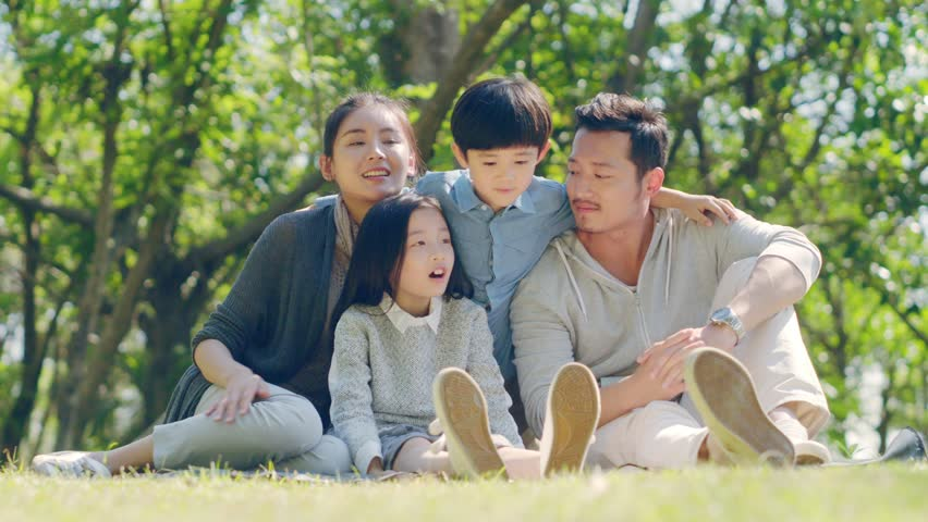 Asian family with two children sitting on grass outdoors in a park talking chatting | Shutterstock HD Video #1022674513