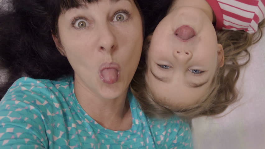 Family selfie. Excited young mother and child playing lying on the bed and taking a selfie. Mother and daughter monkeying around on camera and kissing. Portrait of mom and baby closeup. Slow Motion.