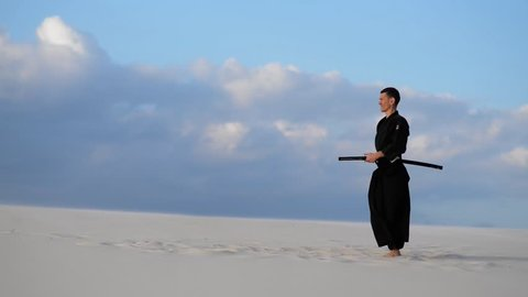 Concentrated man, in traditional Japanese clothes, with sword, katana, is training martial arts in desert during sunset - samurai on the blue cloudy sky background.