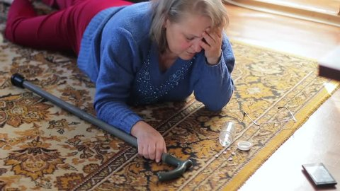 Sick elderly woman lying on the floor and suffering from pain