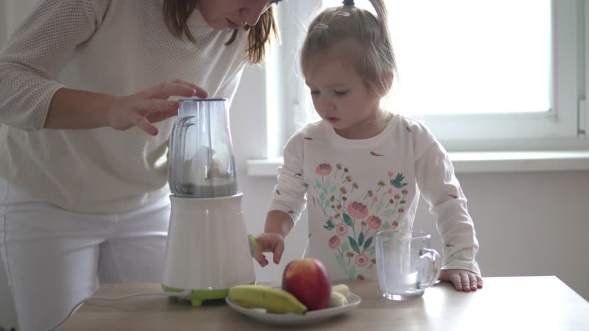 Mom and little daughter are preparing a milkshake. They take the ingredients to the blender. A woman teaches her daughter to cook healthy and natural food at home. | Shutterstock HD Video #1022711473