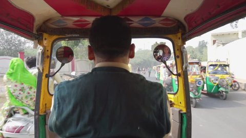 Agra, India - 10 November, 2018: View from back seat of auto rickshaw. Day street traffic. Indian roads and traditional local transport (tuk-tuk). Agra is a popular tourist destination of South Asia.