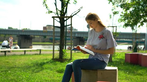 Teenage girl reading book, sitting on bench in city park