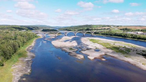 Aerial, drone shot, over a blue river, towards a bridge, on a sunny day, in New Brunswick, Canada