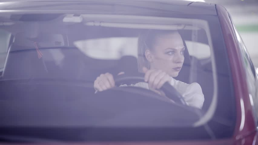 Nice young blonde female with pony tail wearing white classic shirt is sitting in dark red car behind steering wheel when it's starts smoking outside in underground garage.