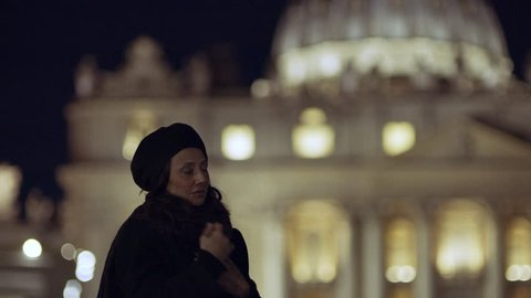 At night in Vatican City, a religious Italian woman walks past St Peter's Basilica, stops and blesses herself. Wide shot on 4k RED camera.
