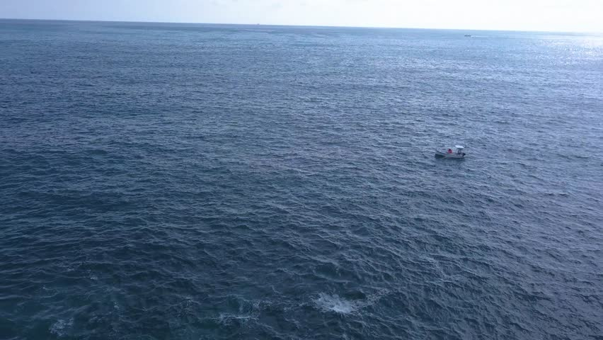 A small boat makes way across the calm blue Mediterranean Sea with a large cargo ship in the distance. Sunlight on the surface of the ocean. Aerial view, drone footage.