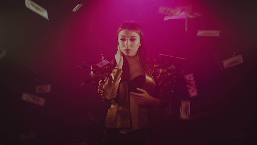 Sexy brunette woman posing alone inside a studio with smoke and floating dollar bills. Rich girl posing under money rain. Shoot with RED RAVEN camera. | Shutterstock HD Video #1022772913