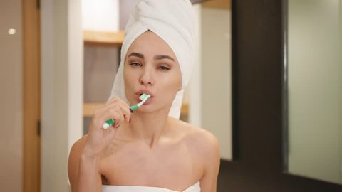 Pretty woman brushing her teeth in modern bathroom / Shot on Red Epic