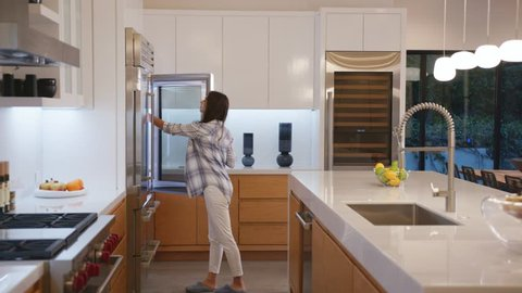 woman walking into the kitchen to take yogurt from refrigerator at night