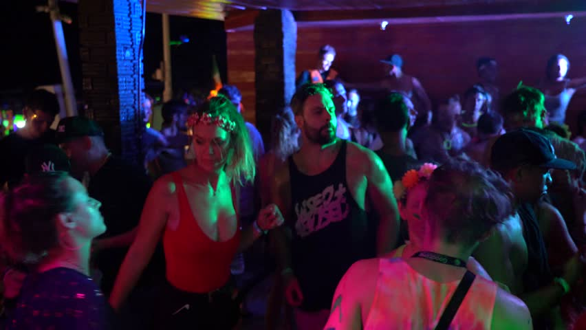 KOH PHANGAN, THAILAND - JANUARY 20, 2019 : Girls and guys participate in Full Moon party in island Koh Phangan, Thailand. Crowds people dance on the sandy beach during the full moon party. Nightlife | Shutterstock HD Video #1022780593